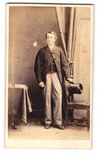Fotografie Hills & Saunders, Eton, Portrait junger Herr im Anzug mit Zylinder in der Hand