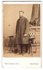 Fotografie Hills & Saunders, Oxford, Portrait Herr mit Vollbart im Mantel mit Regenschirm