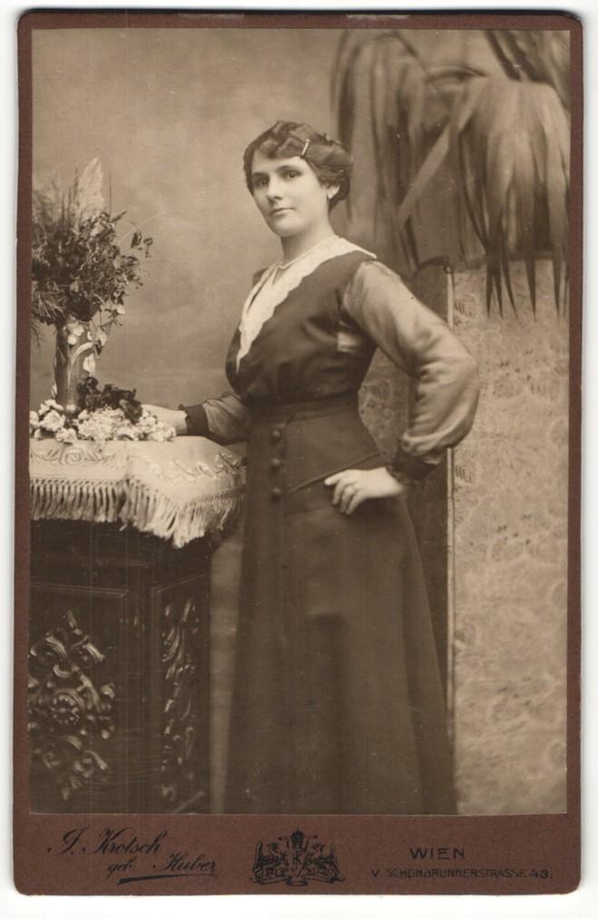 Fotografie J. Krotsch, Wien, Portrait elegant gekleidete Dame mit Blumen an Sockel gelehnt 0