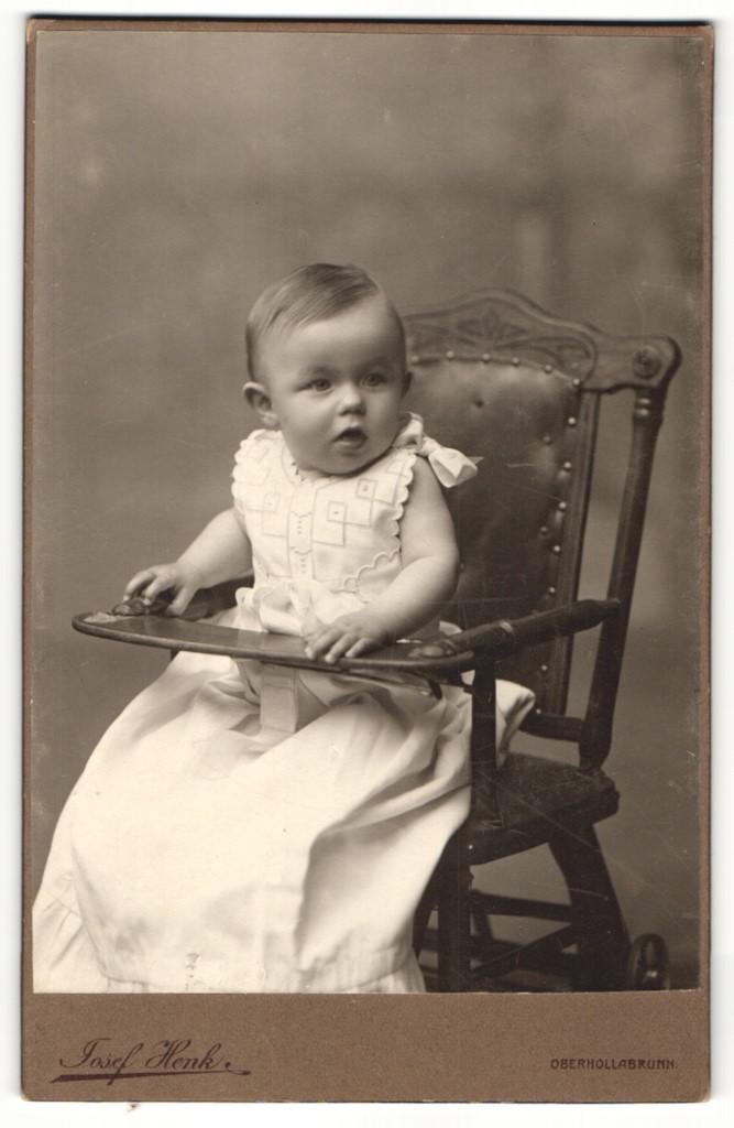 Fotografie Josef Henk, Oberhollabrunn, Portrait niedliches Kleinkind im weissen Kleid im Hochsitz 0