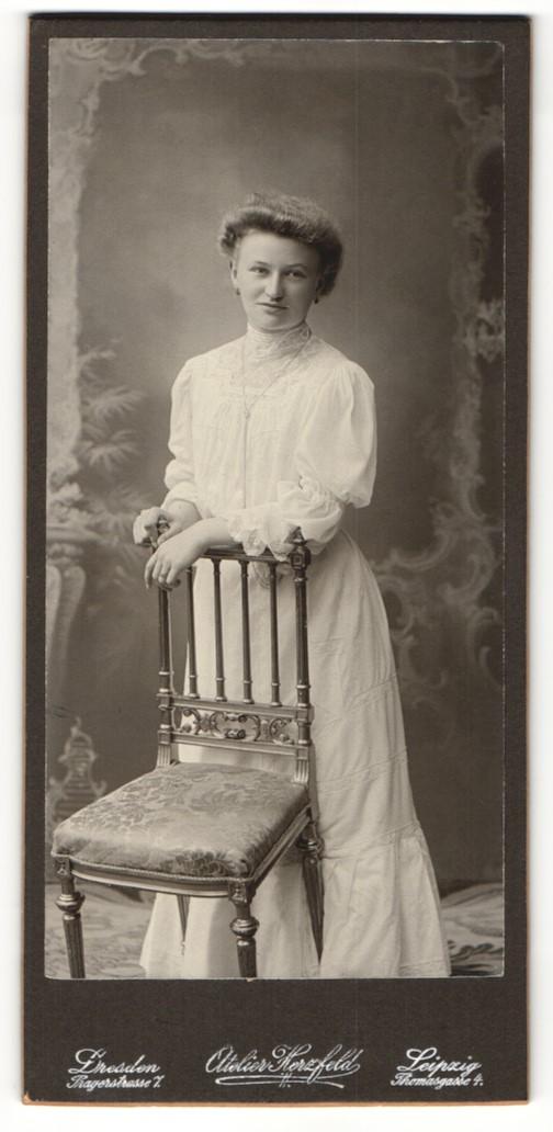 Fotografie Atelier Herzfeld, Dresden, Portrait hübsch gekleidete Dame mit Ohrringen an Stuhl gelehnt 0