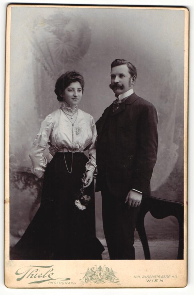Fotografie Robert Thiele, Wien, Portrait bürgerliches Paar in hübscher Kleidung mit Blumen 0