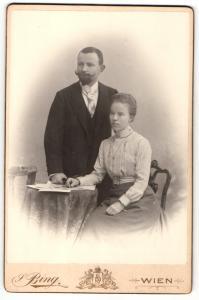 Fotografie Sigmund Bing, Wien, Portrait bürgerliches Paar in modischer Kleidung mit Bildern
