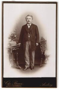 Fotografie Chr. Bauer, Arzberg, Portrait bürgerlich gekleideter Herr mit Hut an Tisch gelehnt