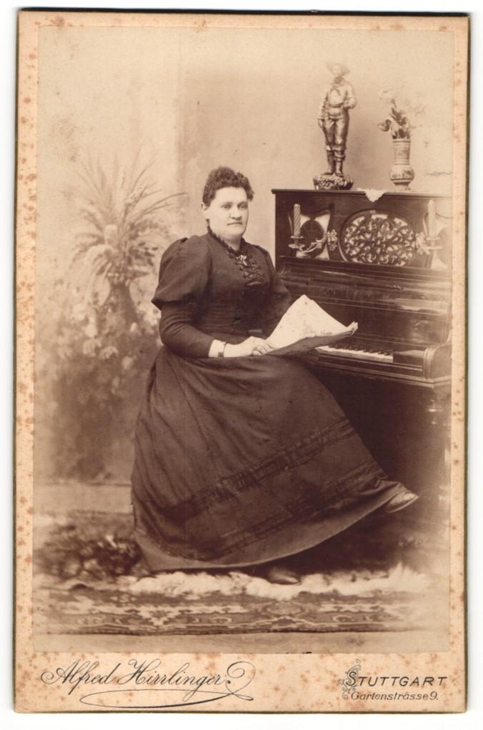 Fotografie Alfred Hirrlinger, Stuttgart, Portrait bürgerlich gekleidete Dame mit Zeitung am Klavier sitzend 0
