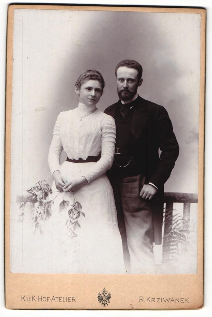 Fotografie R. Krziwanek, Ischl, Portrait elegant gekleidetes Paar mit Zweigen an Geländer gelehnt 0