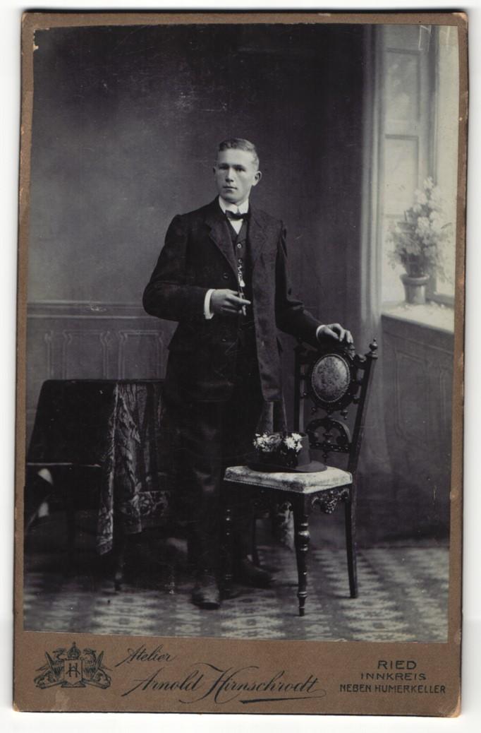 Fotografie Arnold Hirnschrodt, Ried, Portrait elegant gekleideter Herr mit Zigarre an Stuhl gelehnt 0