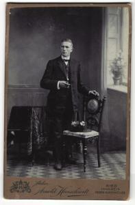 Fotografie Arnold Hirnschrodt, Ried, Portrait elegant gekleideter Herr mit Zigarre an Stuhl gelehnt