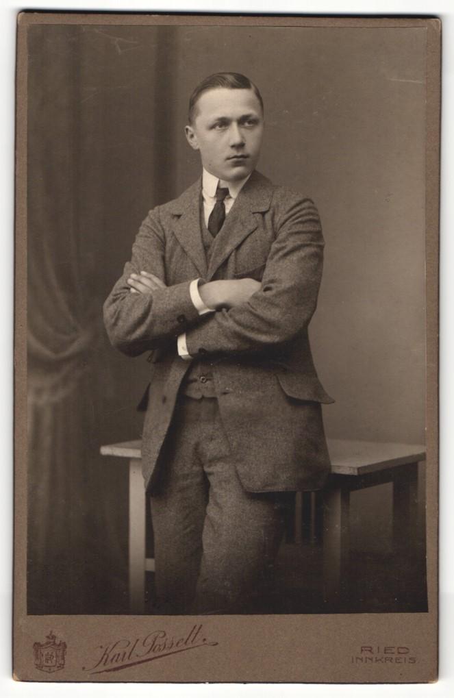 Fotografie Karl Posselt, Ried, Portrait elegant gekleideter Herr mit verschränkten Armen an Tisch gelehnt 0