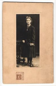 Fotografie Ed. Dickopf, Siegburg, Portrait Konfirmandin mit Gebetsbuch an Tisch gelehnt