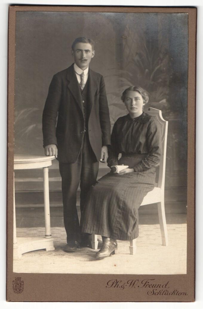 Fotografie Ph. & W. Freund, Schlüchtern, Portrait sitzende Dame in modischer Kleidung mit Heft und Herr im Anzug 0
