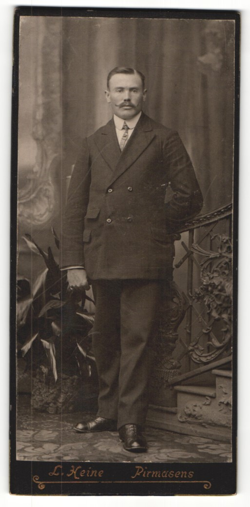 Fotografie L. Heine, Pirmasens, Portrait elegant gekleideter Herr mit Schnauzbart an Geländer gelehnt 0