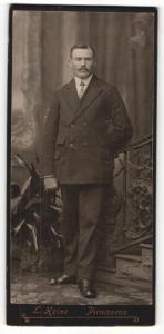 Fotografie L. Heine, Pirmasens, Portrait elegant gekleideter Herr mit Schnauzbart an Geländer gelehnt