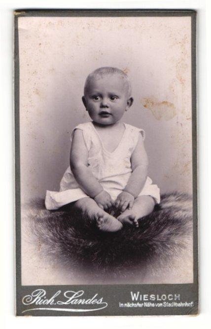 Fotografie Rich. Landes, Wiesloch, Portrait niedlicher kleiner Bube im Hemdchen auf Fell sitzend 0