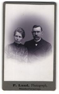 Fotografie P. Lund, Süderbrarup, Portrait elegant gekleidetes Paar
