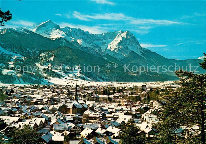 AK / Ansichtskarte Garmisch Partenkirchen Stadtpanorama gegen Zugspitze Wettersteingebirge Winterlandschaft Garmisch Partenkirchen