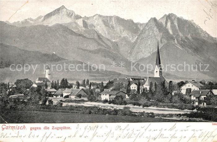 AK / Ansichtskarte Garmisch Partenkirchen Ortsansicht mit Kirche gegen Zugspitze Wettersteingebirge Garmisch Partenkirchen