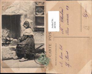 487434,Kind Mädchen m. Blasebalg Holzschuhe vor Kamin Ofen