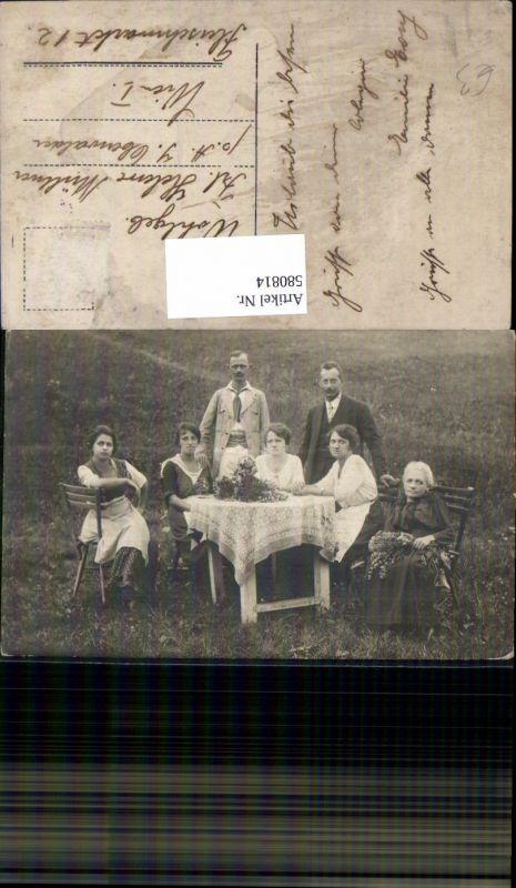 580814,Gruppenbild Familie b. Tisch Blumenstrauß